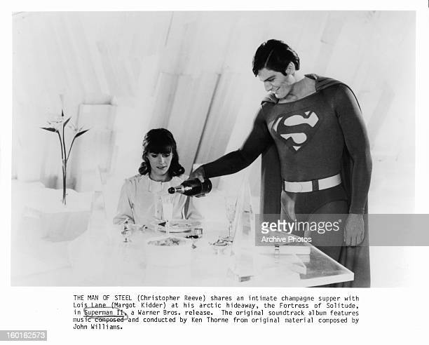 Margot Kidder watches as Christopher Reeve pours her a glass of champagne in a scene from the film 'Superman II' 1980