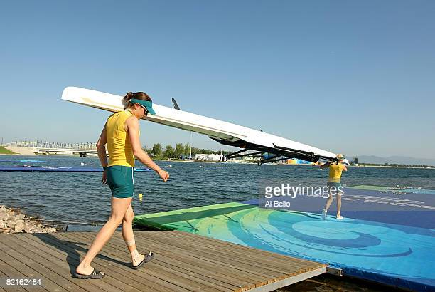 Marguerite Houston and Amber Halliday of Australia carry their boat to the water as they practice for the light weight double sculls at the Shunyi...