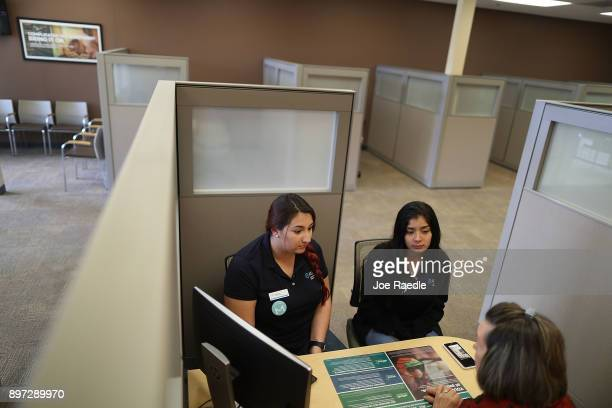 Marguerite Salmon HR Block tax specialist speaks with Melanie Gonzalez and Andrea Santin as she helps them with tax advice on the day President...