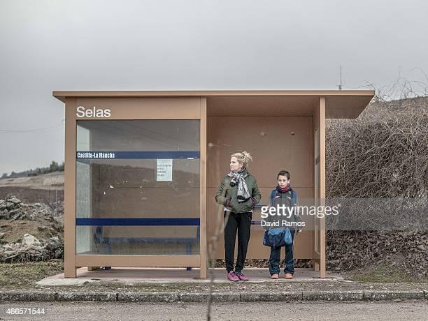Mari Angeles Moreno and her son Juan Romero wait for the school bus outside the village of Selas on February 23 2015 near Molina de Aragon Spain Juan...
