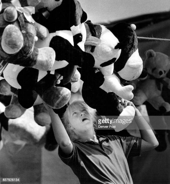 Mari Boggess puts up stuffed animals at the ring toss at McNichols for the Spring Festival Credit The Denver Post