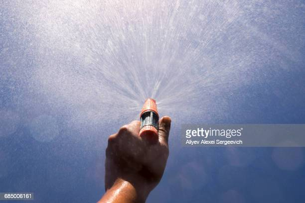 Mari boy spraying nozzle to blue sky
