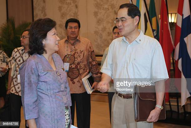 Mari Elka Pangestu Indonesia's minister of trade left chats with Lim Hng Kiang Singapore's minister of trade prior to the start of the Informal Trade...