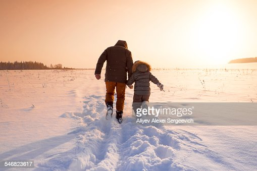 Mari father and son walking in snowy field