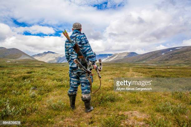 Mari hunter carrying crossbow in remote field