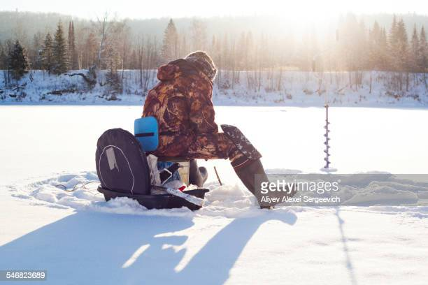 Mari man ice fishing in snowy field