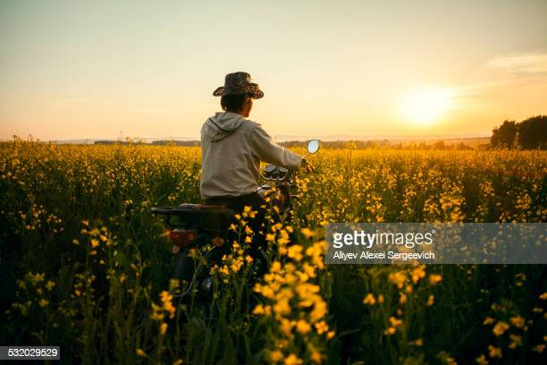 Mari man riding motorcycle in field of flowers
