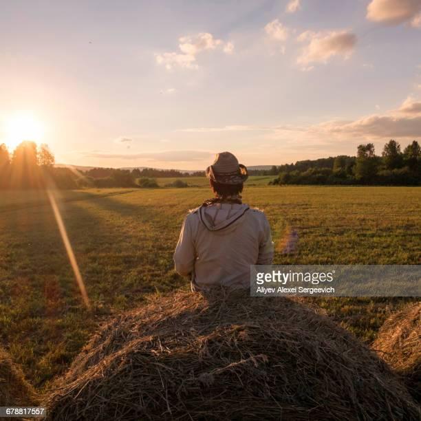 Mari man sitting on hay bale at sunset