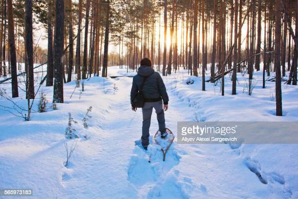 Mari man snowshoeing on snowy path