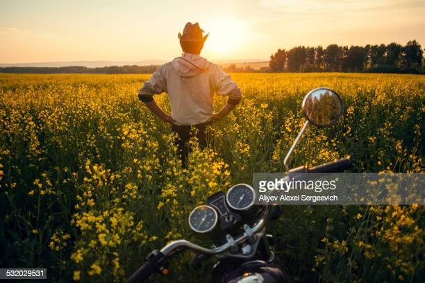 Mari man standing near motorcycle in field of flowers
