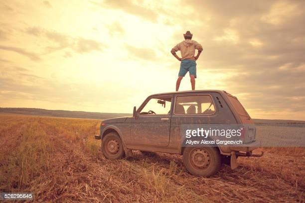 Mari man standing on car roof in rural field