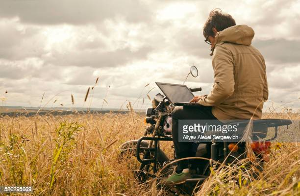 Mari man using laptop on motorcycle in rural field