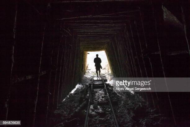 Mari man walking on tracks in mine