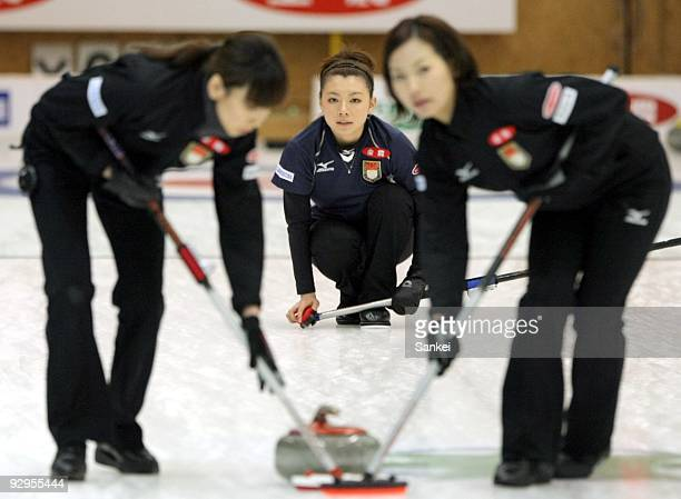 Mari Motohashi of Team Aomori has her stone swept by her teammates against Team Nagano during women's curling Vancouver Olympic qualifying at Aomori...