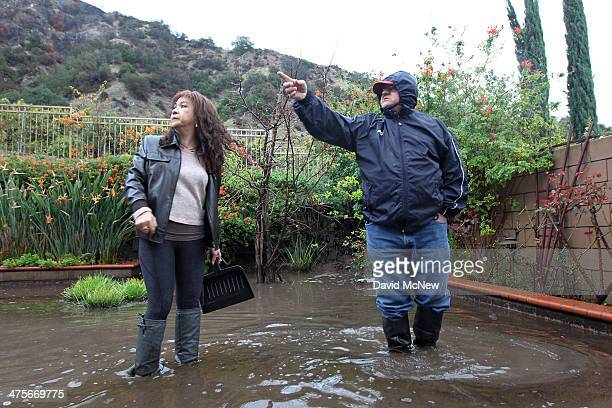 Mari Poblete and neighbor Lorenzo Tatone look at hillsides from which ash water and mud flow through her yard below the Colby Fire burn area as a...