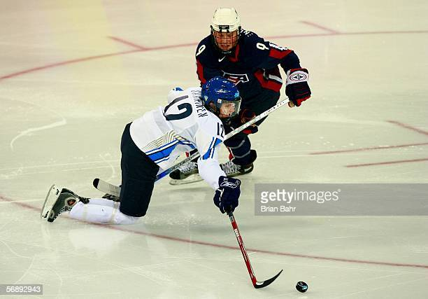 Mari Saarinen of Finland and Molly Engstrom of the United States fight for the puck during the women's ice hockey bronze medal match during Day 10 of...