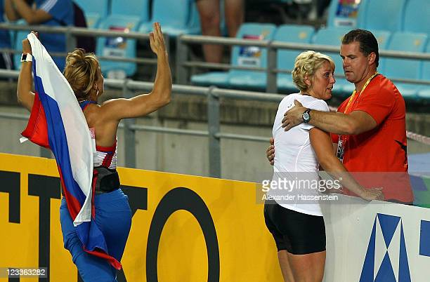 Maria Abakumova of Russia celebrates victory in the women's javelin final as Christina Obergfoll of Geermany cries in the arms of her boyfriend Boris...