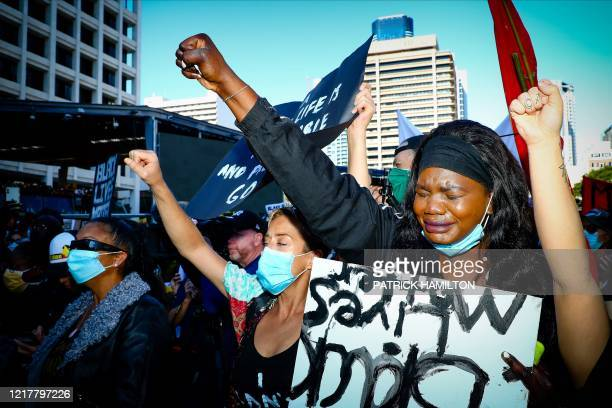 Maria Achan gives a 'Black Power' salute during a Black Lives Matter protest to express solidarity with US protestors at King George Square in...