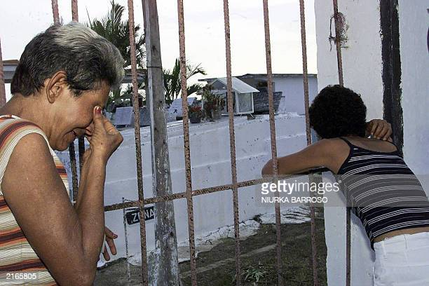 Maria Acosta Valdes and Caridad Acosta Placeres the mothers of Luis Alberto Suarez and Yosvani Martinez respectively cry in front of the locked gate...