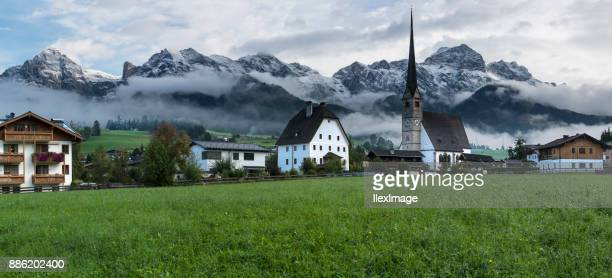 maria alm austria steeple with snow capped mountains panorama - saalfelden stock pictures, royalty-free photos & images
