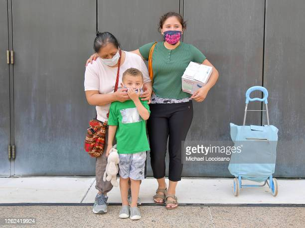 Maria and her family are one of many New Yorkers in need to receive free produce dry goods and meat at a Food Bank For New York City distribution...