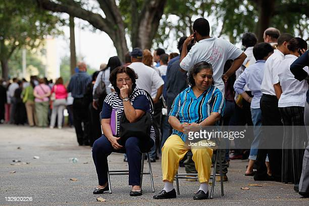 Maria and Nikki Picante sit as they wait in line with other job seekers line up to apply for an opening with Major League Baseball's Miami Marlins on...