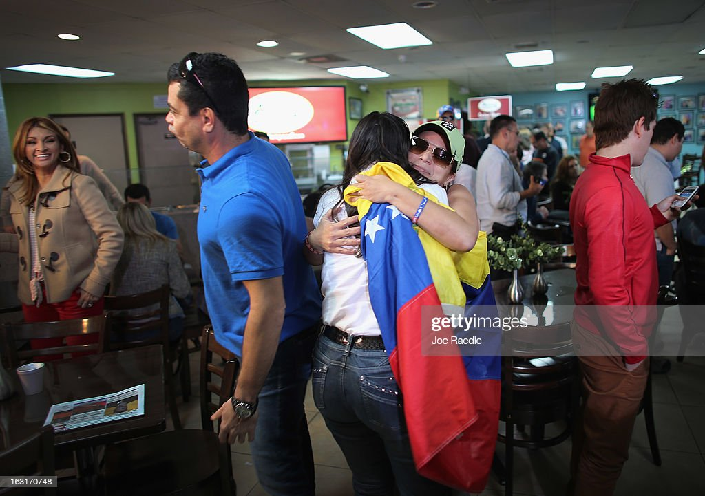Maria Antieta (R) holds a Venezuelan flag as she is hugged while listening to television sets reporting on the death of Venezuelan president Hugo Chavez, at El Arepazo 2 a restaurant in the heart of a neighborhood that has the largest concentration of Venezuelans in the U.S. on March 5, 2013 in Doral, Florida. The Venezuelan government announced today that Hugo Chavez lost his battle with cancer.