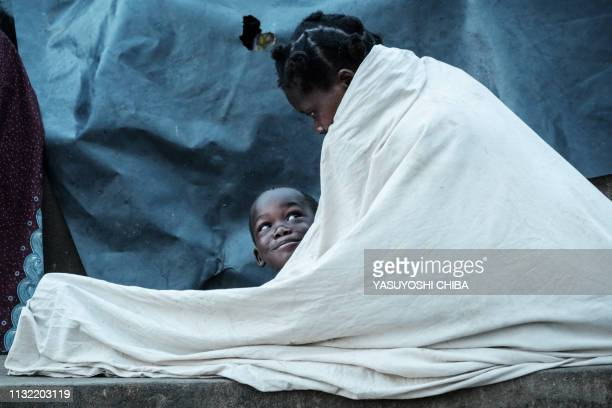 TOPSHOT Maria Armando and her son Fernando Emmanuel wake up as they stay in shelter at the stands of Ring ground in Buzi Mozambique on March 23 2019...