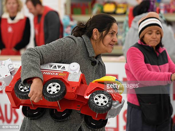 Maria Balacaos carries away a toy firetruck while shopping at the 86th annual Denver Santa Claus Shop at the old Kmart store near Evans Ave and...