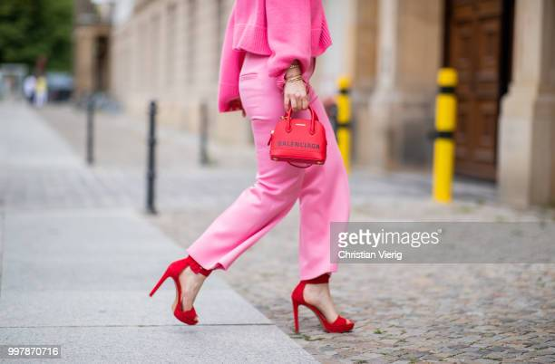 Maria Barteczko is seen wearing a pink oversized cashmere sweater Celine, pink cropped wool trousers Celine, red plateau sandals Steve madden, red...