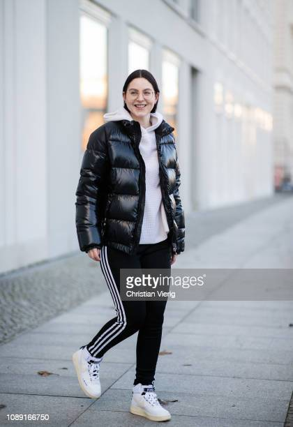 Maria Barteczko is seen wearing black puffer jacket Pyrenex light beige cashmere hoodie Elizabeth James black striped track suit pants Adidas white...