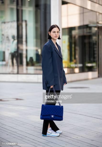 Maria Barteczko is seen wearing dark blue oversized blazer Dior, white silk cropped top Saint Laurent, black flared leggings Zara, silver chunky...