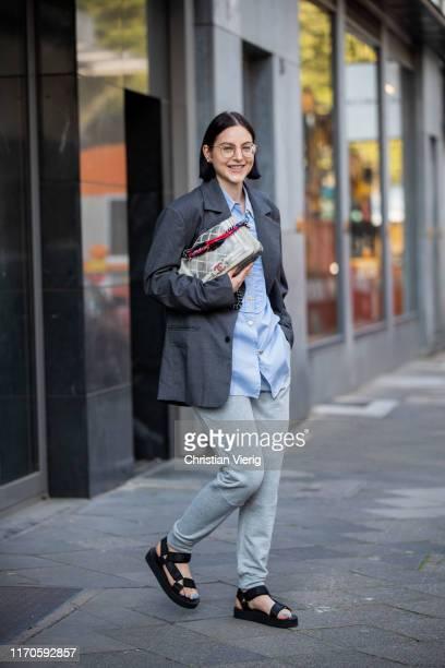 Maria Barteczko is seen wearing grey oversized blazer Badblood blue striped blouse Chanel grey sweatpants Nike black chunky hiking sandals Asos...