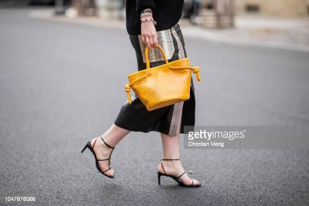 Maria Barteczko wearing a black oversized casmhere sweater Iris von Arnim leather pencil skirt By Malene Birger yellow bucket bag Ruigrok van der...