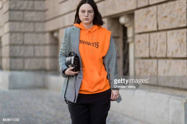 Maria Barteczko wearing orange hoodie Wasted Paris oversized checked blazer in grey Stella McCartney wide leg black trousers HM black heels Gianvito...