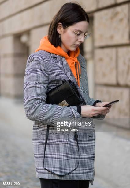 Maria Barteczko wearing orange hoodie Wasted Paris oversized checked blazer in grey Stella McCartney wide leg black trousers HM black heels Gianvito...