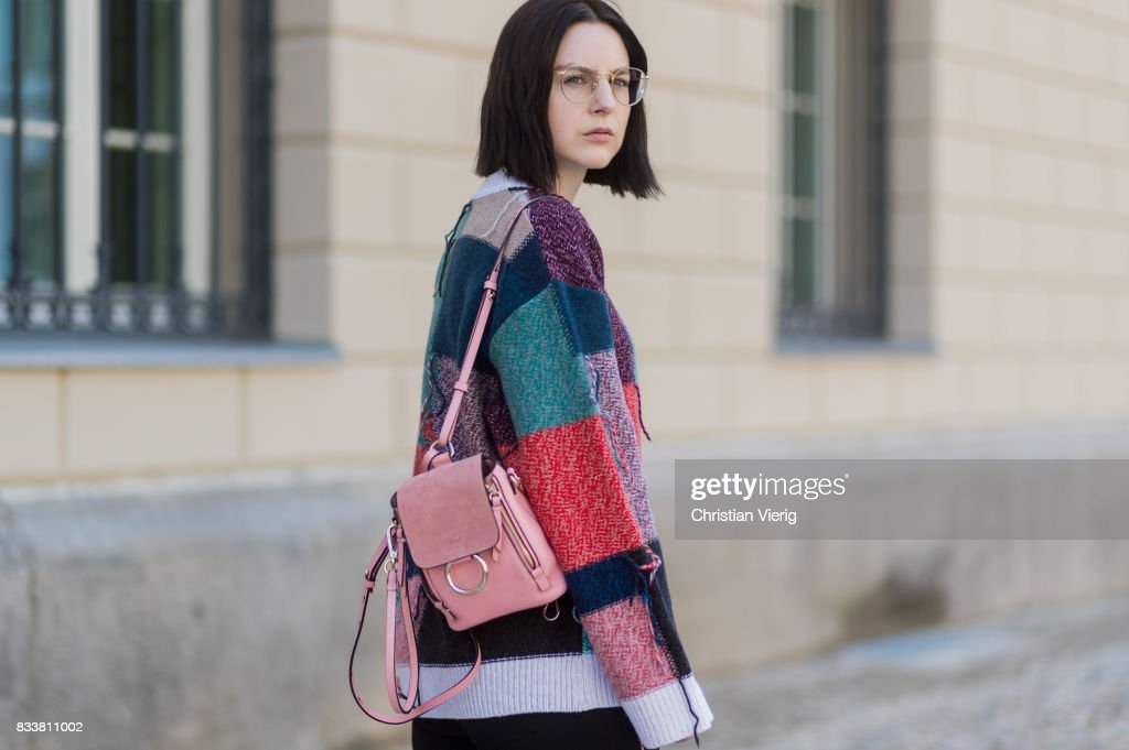 Maria Barteczko wearing patchwork oversized wool sweater Stella McCartney, black skinny jeans Madewell, red buckle boots with studs Givenchy, silver knot bracelet Celine, mini Faye backpack in light rose Chloe, round gold glasses Ray Ban on August 17, 2017 in Berlin, Germany.