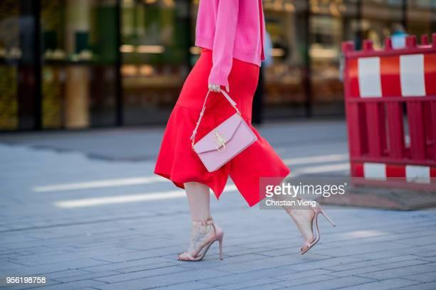 Maria Barteczko wearing pink cashmere sweater Valentino red silk asymmetric midi skirt Victoria Beckham light pink bag JW Anderson light pink satin...