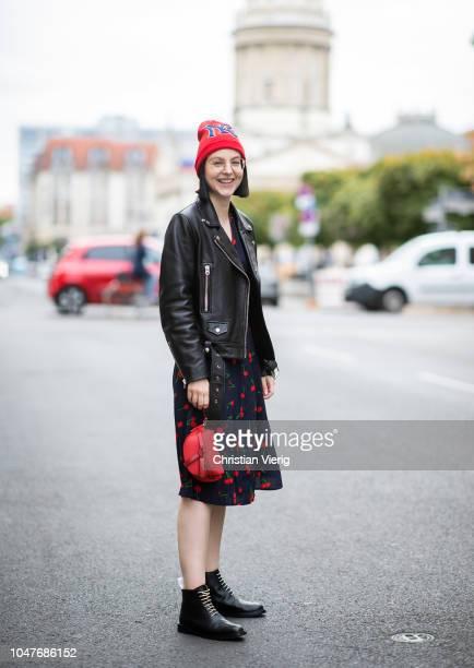 Maria Barteczko wearing red beanie Gucci teale cherry printed dress Realisation Par black biker leather jacket Acne Studios red mini bag Loewe gold...