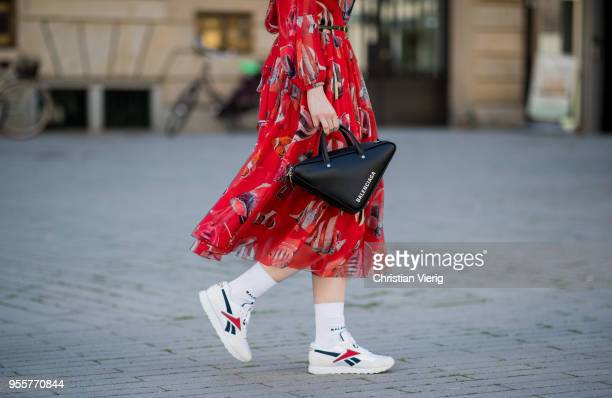 Maria Barteczko wearing red printed maxi dress Dolce Gabbana white socks Balenciaga white sneakers Reebok black triangle bag Balenciaga black cat eye...