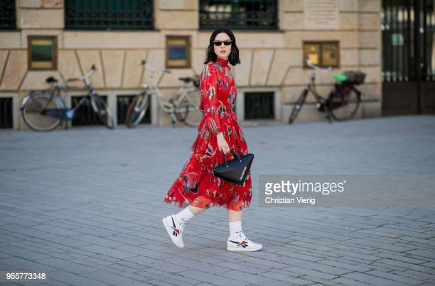 Maria Barteczko wearing red printed maxi dress Dolce Gabbana white socks Balenciaga white sneakers Reebok black triangle bag Balenciaga black cat eye...