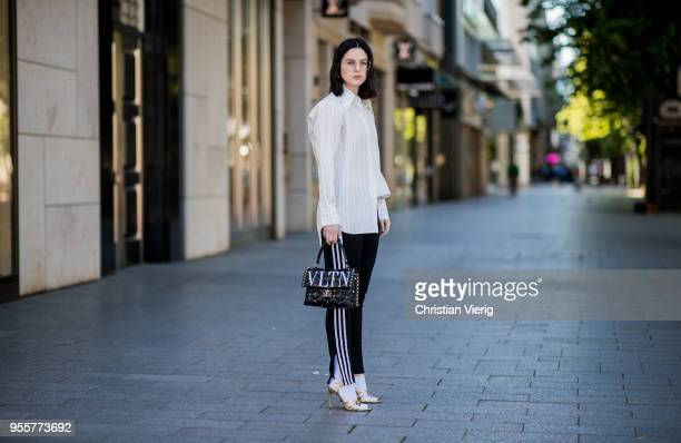 Maria Barteczko wearing white striped silk blouse Celine black striped pants Adidas white socks Balenciaga black studded bag Valentino gold metallic...