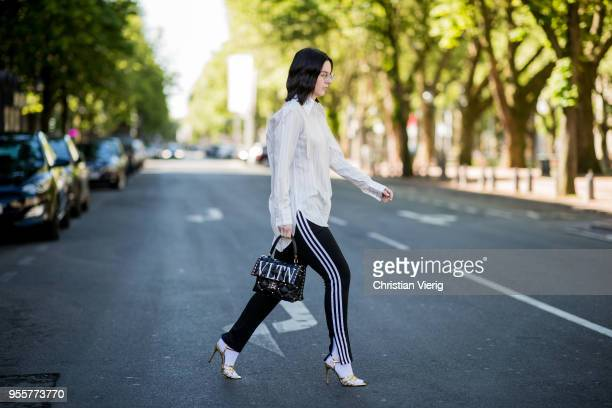 Maria Barteczko wearing white striped silk blouse Celine black striped pants Adidas white socks Balenciaga black studded bag Valentino gold metallic...