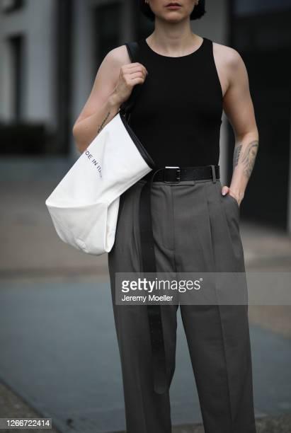Maria Barteczko wearing Zara black body, Pixie Market grey pants, Celine oversized canvas tote bag on August 15, 2020 in Dusseldorf, Germany.