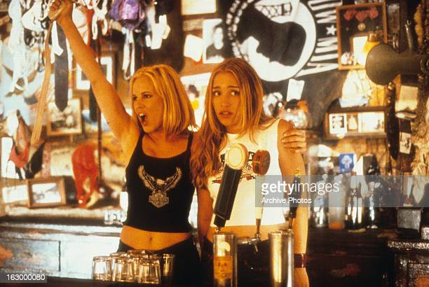 Maria Bello grabbing hold of Piper Perabo as she cheers on the crowd in a scene from the film 'Coyote Ugly' 2000