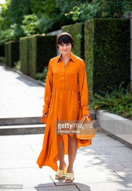 Maria Bernad is seen wearing assymetric orange dress bag hair loop outside Mykke Hofmann during Copenhagen Fashion Week Spring/Summer 2020 on August...