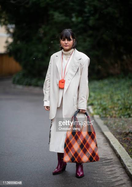 Maria Bernad is seen wearing checked multi colored bag creme white wide leg pants blazer orange Jacquemus mini bag outside By Malene Briger during...