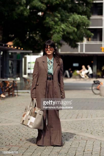 Maria Bernad wearing brown suit outside MKDT during Copenhagen fashion week SS22 on August 12, 2021 in Copenhagen, Denmark.