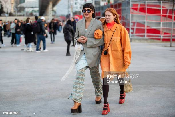 Maria Bernad wearing grey blazer striped flared pants, brown shoes with heels and Courtney Trop wearing orange jacket, mini Jacquemus bag seen...
