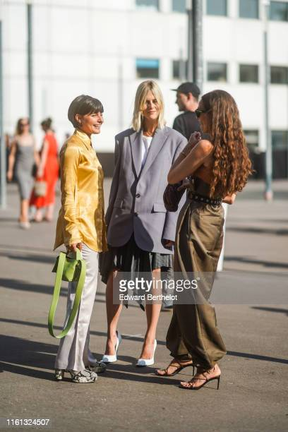 Maria Bernad wears a black headband a lustrous yellow satin shirt lustrous lightgrey flare pants a pistachiogreen bag grey python pattern platform...